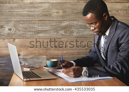 Wealthy and serious dark-skinned businessman with laptop checking report in cafe with a cup of coffee. Young African entrepreneur is focused on work issues and signing papers for business deals. - stock photo