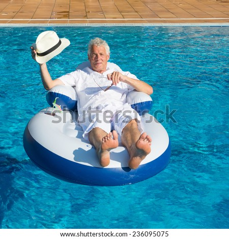 wealthy man relaxing in own swimming pool - stock photo