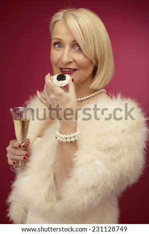 Wealthy Mature Woman Holding Champagne and Caviar - stock photo