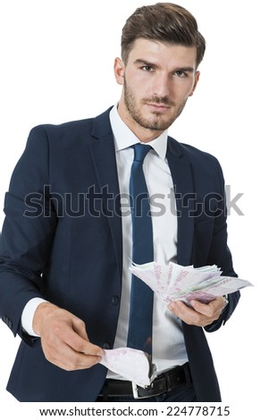 Wealthy successful stylish young businessman burning money from a handful of euro banknotes with a happy smile showing off his affluence, isolated on white - stock photo