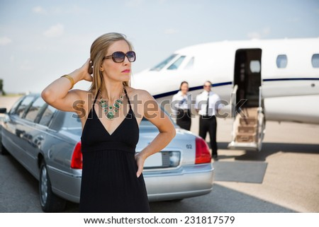 Wealthy woman in elegant dress standing against limousine and private at terminal - stock photo