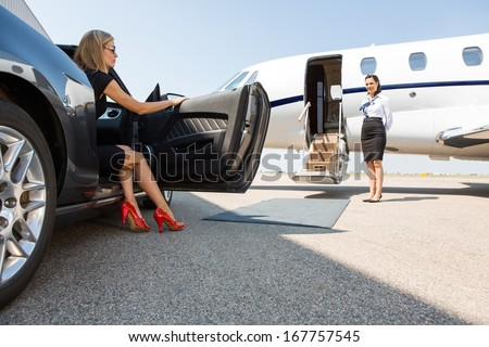 wealthy woman stepping out of car parked in front of private plane and airhostess - stock photo
