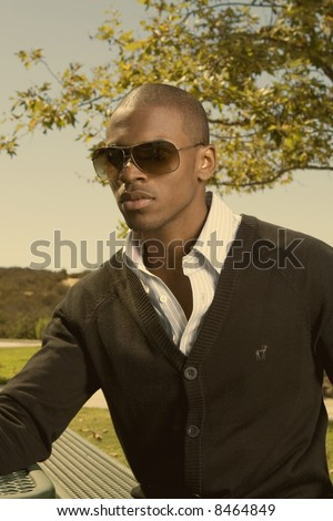 wealthy young black man sitting in a park with sun glasses - stock photo