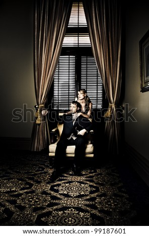 Wealthy young retro couple posing before luxurious gold curtains for a portrait in their lavish family home in a depiction of fortune, riches and wealth - stock photo