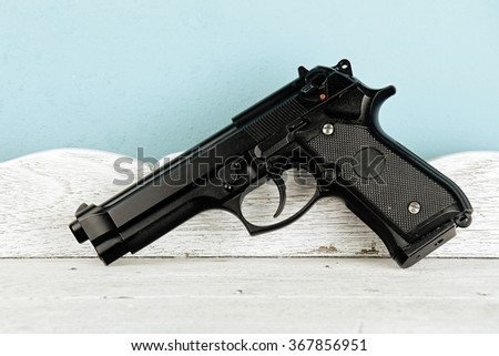 Weapon series. Modern U.S. Army handgun close-up on vintage wooden table background. pistols - stock photo