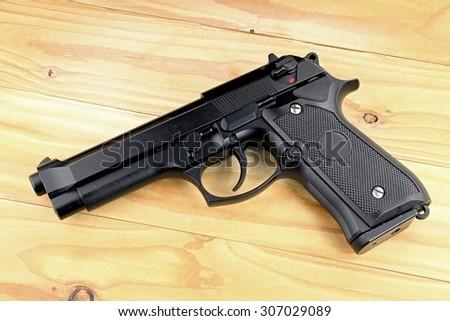Weapon series. Modern U.S. Army handgun M9 close-up on grey wooden background. - stock photo