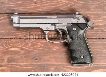 Weapon series. Modern U.S. Army handgun M9 close-up.  on wood background.  - stock photo