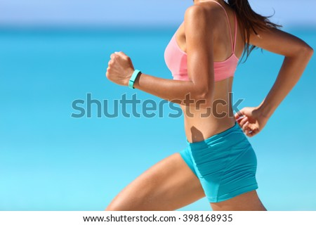 Wearable tech smart watch closeup, active woman wearing activity tracker bracelet on wrist. Runner girl running fast intense run outdoor on beach ocean background living a healthy life. Legs closeup.
