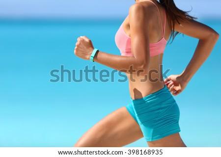Wearable tech smart watch closeup, active woman wearing activity tracker bracelet on wrist. Runner girl running fast intense run outdoor on beach ocean background living a healthy life. Legs closeup. - stock photo