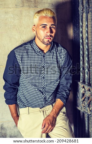 Wearing a black patterned shirt, yellow pants, a young man with beard, yellow hair is leaning against the wall outside a metal gate, seriously looking at you. - stock photo
