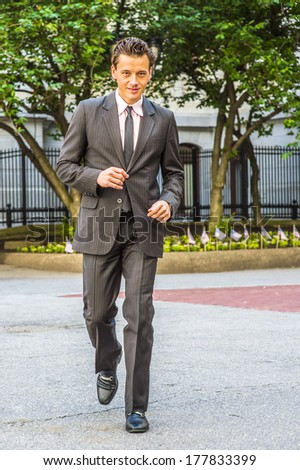 Wearing a black striped jacket, pants, tie, leather shoes,  a young businessman is confidently walking toward you. / Businessman Walking  - stock photo