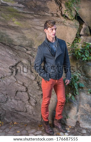 Wearing a blue slim fit jacket, red jeans, brown leather boot shoes, a young guy is standing by a rocky wall, patiently waited. / Waiting for You