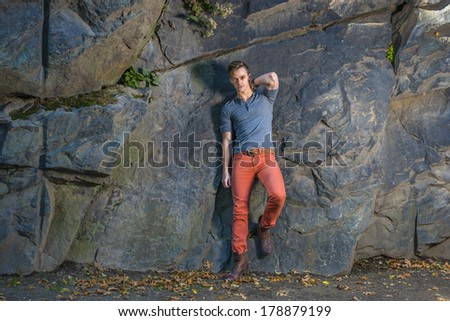 Wearing a gray long sleeves with roll-tab Henley shirt,  red jeans, brown leather boot shoes, a young guy is leaning on big rocks, looking at you. / Portrait of Young Guy - stock photo
