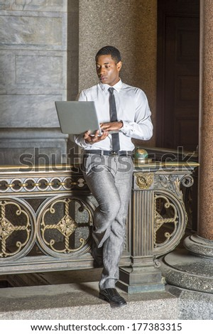 Wearing a white shirt, a black tie, gray pants, a young handsome black college student is standing by a railing in a hallway on a campus, working on a laptop computer. / Study Anywhere - stock photo
