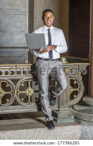 Wearing a white shirt, a black tie, gray pants, holding a laptop computer, a young handsome black college student is standing by a railing in a hallway on a campus, smiling, looking at you.  - stock photo