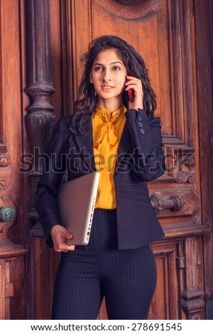 Wearing black blazer, orange under shirt, a young East Indian American business woman standing by vintage style office door way, arm carrying laptop computer, listening, talking on her mobile phone. - stock photo