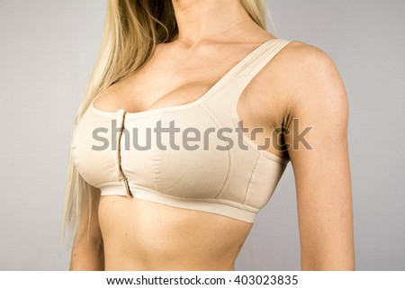 Wearing bra. Close-up of women wearing bra beautiful part of female body. Breast care. Perfect woman's form, flat belly, sexy breasts in beige bra lingerie. Healthy lifestyle, smooth skin, diet, sport - stock photo
