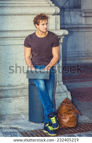 Wearing dark brown T shirt, blue jeans, black sneakers, leather bag on the ground, a young sexy guy with curly hair is sitting on a metal stake on the corner, working on laptop computer, thinking.  - stock photo