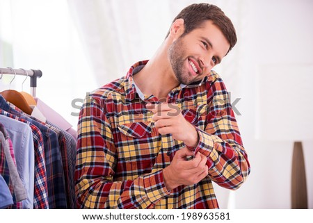 Wearing his favorite shirt. Handsome young man wearing shirt and talking on the mobile phone