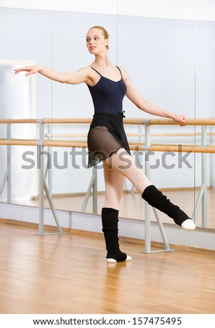 Wearing leotard and warmers ballet dancer dances near barre and mirrors in studio