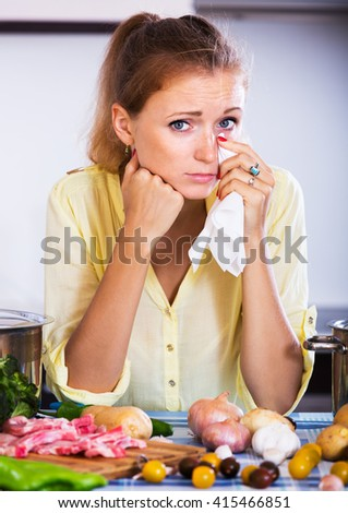 Weary girl with meat and vegetables at kitchen table