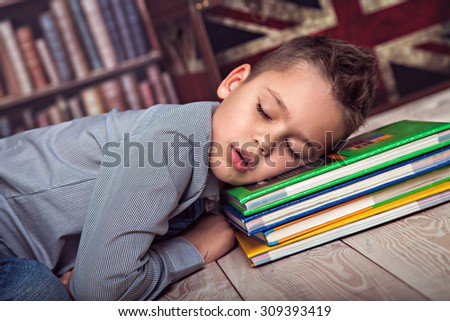 Weary primary schoolboy fallen asleep on books - stock photo