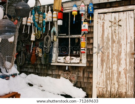 Weather beaten and worn doorway of a lobsterman's fishing shack with colorful buoys - stock photo