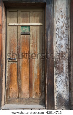 Weather beaten door on an old wooden building