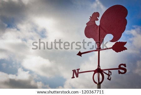 Weather cock against a cloudy sky - stock photo
