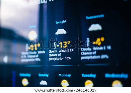 Weather forecast interface on a modern digital display showing cold weather for the next days. Tilt-shift lens used to outline the cold -13 symbols. - stock photo