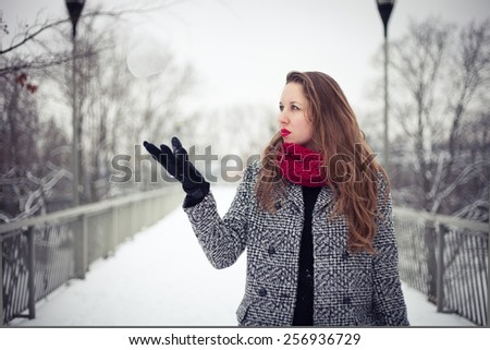 Weather forecaster: young woman throwing a snowball in the air - stock photo