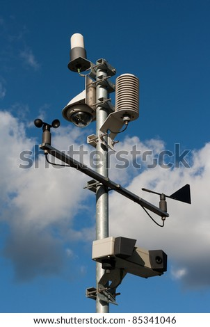 Weather station against blue cloudy sky - stock photo
