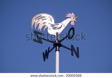 Weather vane - cockerel which reflected sun against bright-dark blue sky - stock photo