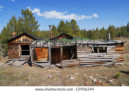 Weathered abandoned home in remote mountain meadow.