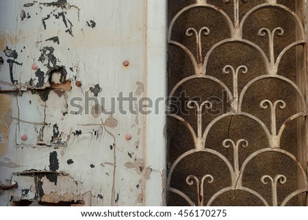Weathered abandoned house old door with rusty metal pattern and broken chipped wood background texture. - stock photo