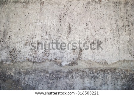 Weathered, aged and cracked gray stone wall with names scratched on it. - stock photo