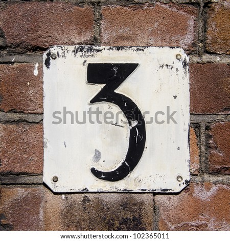 weathered and crackled house number three on a brick wall - stock photo