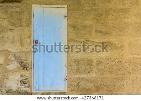 Weathered blue wooden door with a metallic rusty lock textured with paint chipped and peeling.