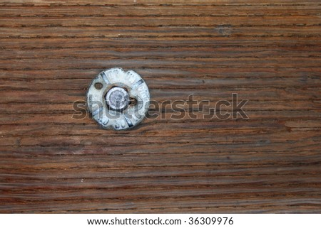 Weathered bolt in a piece of timber from a wooden pier