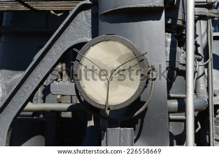 Weathered electrical headlight of a steam locomotive. Electrical bulb inside the cage. Metal constructions and frames in the background - stock photo