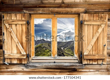 Weathered facade of a mountain hut with summer mountain reflections - stock photo