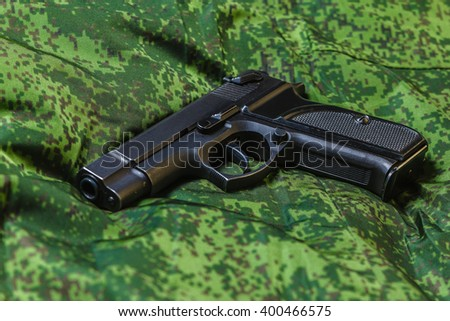 Weathered generic russian soviet semi-automatic 9mm pistol on pixel camouflage background - stock photo