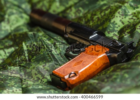 Weathered generic russian soviet semi-automatic 9mm silenced  pistol on pixel camouflage background - stock photo