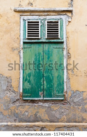 Weathered green window shutters. Weathered green window shutters and old wall with pealing paint and cracking plaster. Photographed in Willemstad, Curacao, Netherlands Antilles. - stock photo