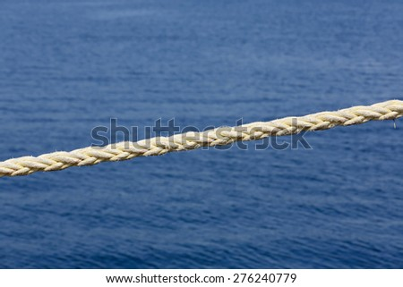 Weathered harbor rope against a blue ocean background  - stock photo