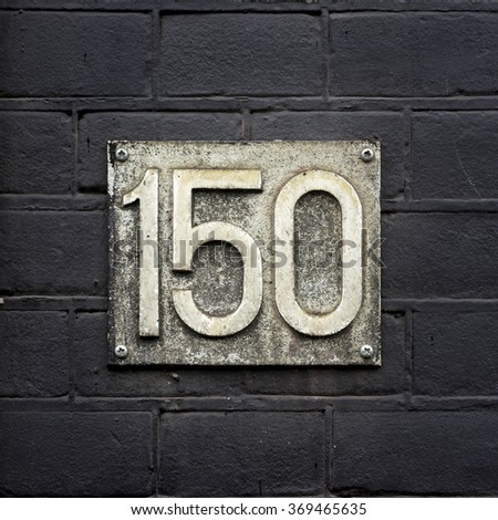 weathered house number one hundred and fifty - stock photo