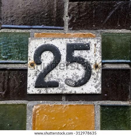 Weathered house number twenty five on a wall with glazed bricks - stock photo