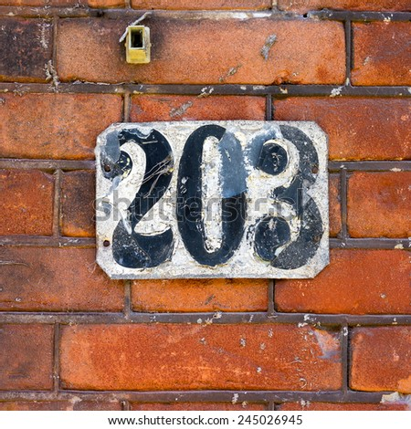 weathered house number two hundred and three. - stock photo