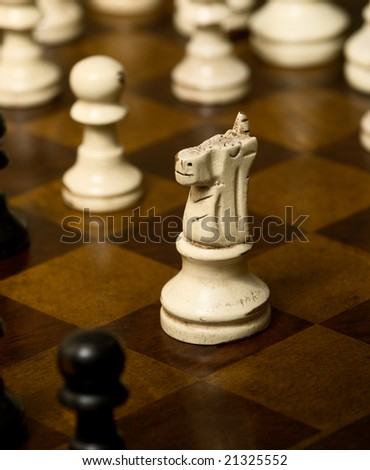 Weathered knight rides into battle on a chess board