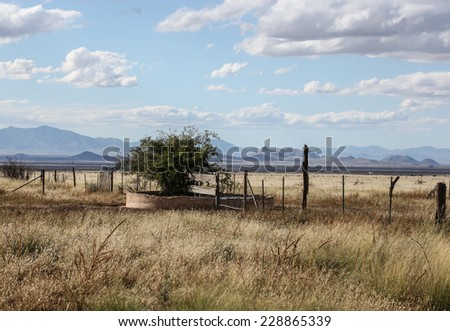 Weathered old concrete stock tank with water for livestock in semi-desert grasslands/Old Handmade Cement Stock Pond with Water for Cattle in Dry Rural Grassland Prairie/Old cement stock dam for cattle - stock photo
